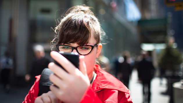 woman-using-smartphone-street-getty-images