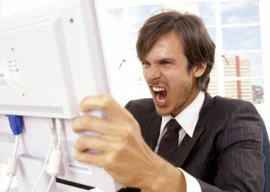 Businessman yelling at a computer monitor