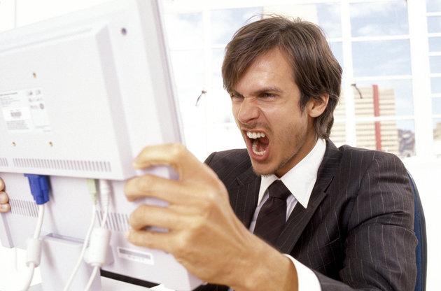 Businessman yelling at a computer monitor
