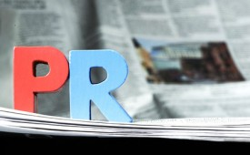 27214281 - word pr on newspaper. wooden letters